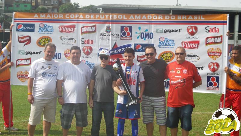 Guilhermo, capitão do Centro de Futebol Zico, recebe a taça de campeão