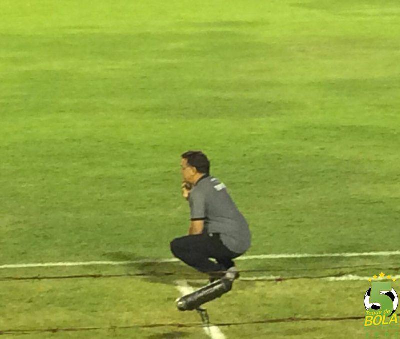 Agachaado, Estevam Soares observa o primeiro tempo da partida próximo ao banco de reservas carijó